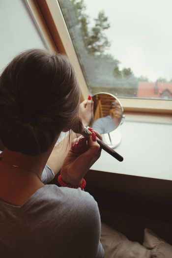 Rear view of young woman applying make-up against window at home