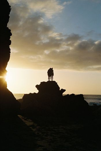 Silhouette sculpture on rock at beach against sky during sunset