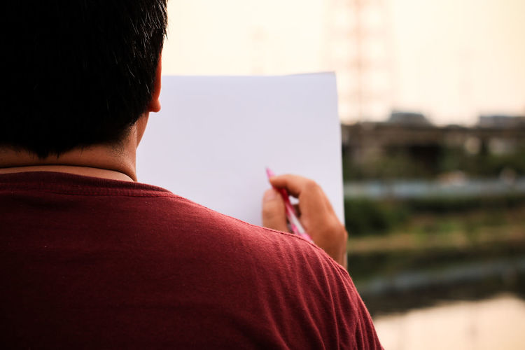 Rear view of man with blank paper in city during sunset