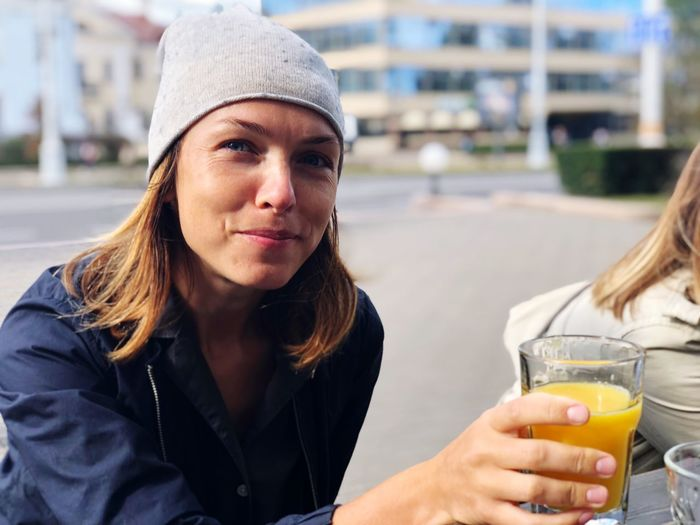 EyeEm Selects Real People Front View Lifestyles Drink Leisure Activity Focus On Foreground Adult Hat Young Adult Smiling Headshot Glass Young Women Portrait Refreshment People Food And Drink Outdoors Women Day