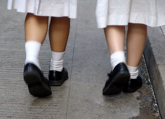 Low section of girls wearing school uniform walking on sidewalk