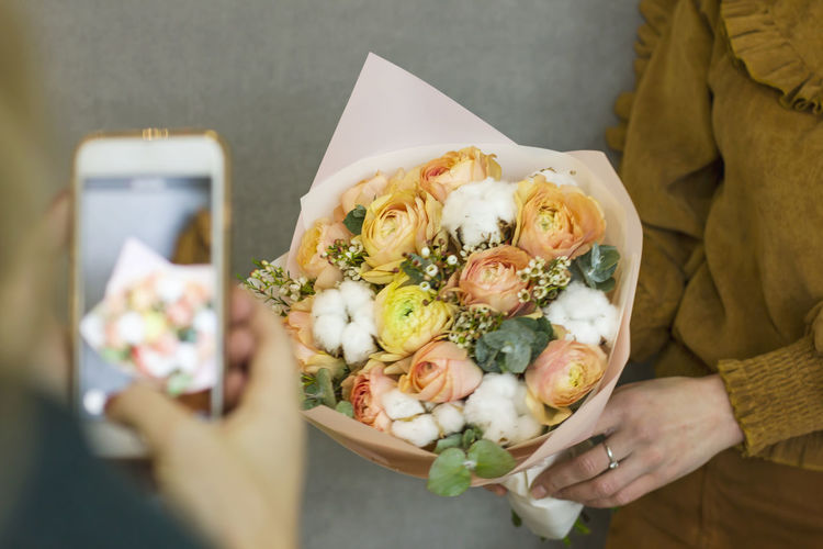 Midsection of woman holding flower bouquet