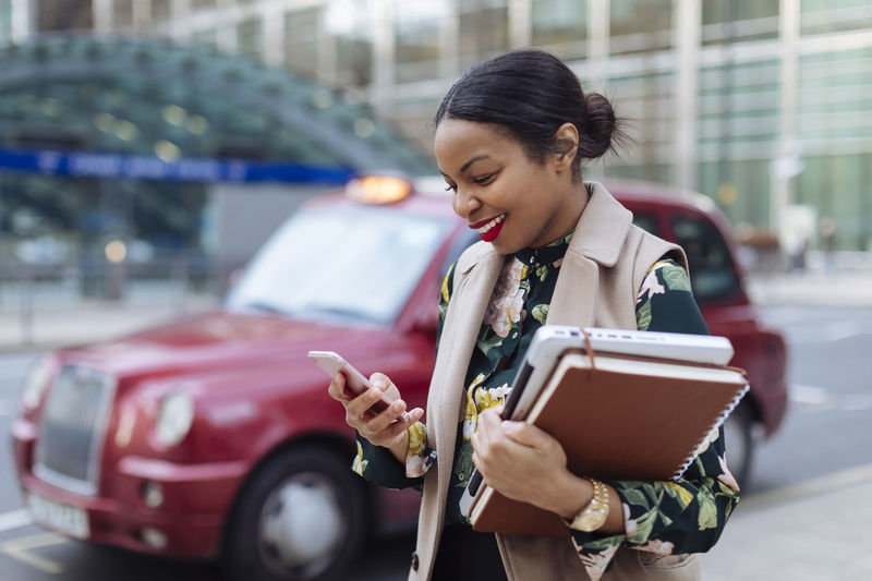 Woman holding mobile phone in city