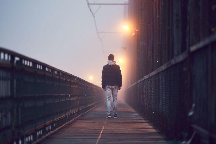 Rear view of man on footbridge against sky