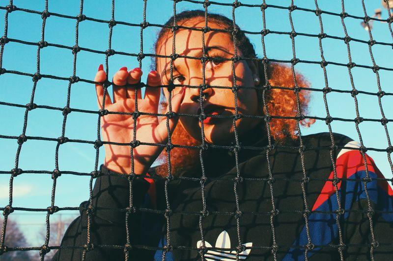 Portrait of man seen through chainlink fence