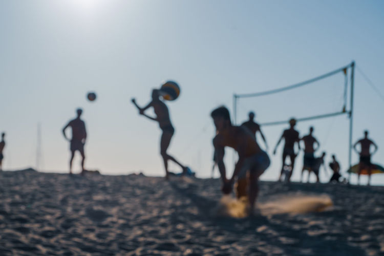 People playing at beach against clear sky