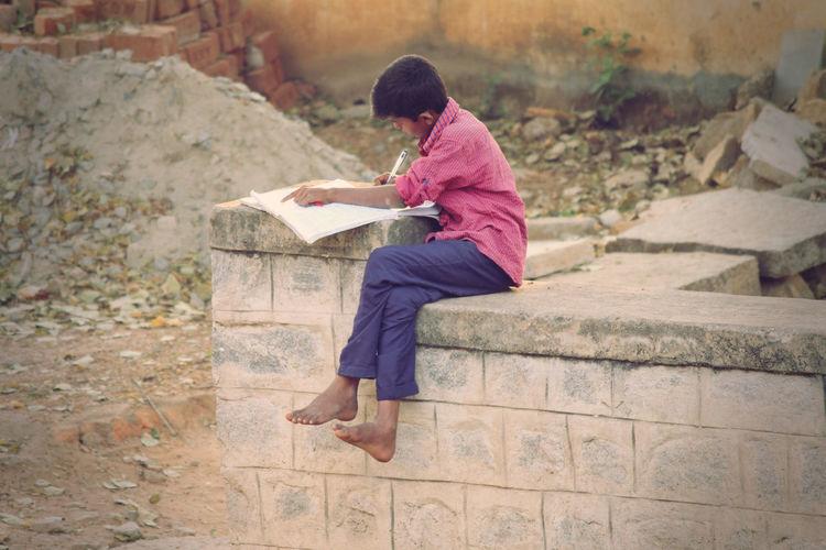 Boy studying while sitting at abandoned damaged retaining wall