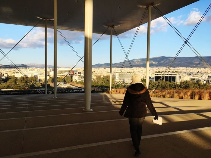 Full length rear view of woman standing in city against sky