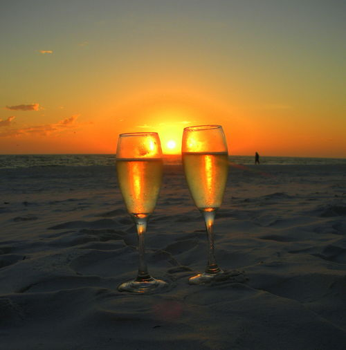 CHAMPAGNE GLASSES ON BEACH AT SUNSET