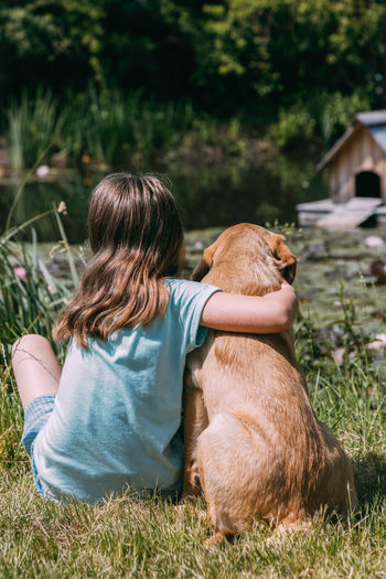 Friendship of animals and children, people.girl sits on the bank of a pond and hugs a labrador puppy