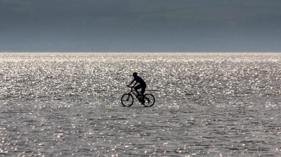Silhouette man cycling at beach