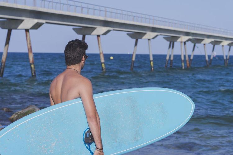 Young surfer posing with his surfboard seaside Alone Fun Lifestyle M Man Mediterranean  Millennial Pink Surfer Wafest Beach Board Coast Joy Outdoors People Portrait Sea Sport Summer Surface Level Surfboard Trendy Water Waves Wet