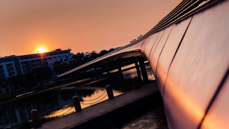 Train on railroad bridge against sky during sunset