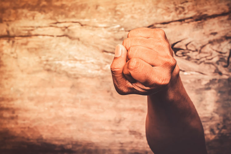 A man fists clenched on a wooden table in anger Human Body Part Human Hand Hand One Person Real People Men Body Part Focus On Foreground Lifestyles Close-up Wall - Building Feature Day Finger Human Finger Selective Focus Human Limb Holding Top View Vintage Majestic Man Males  Fists Clenched Fists Clenched Clenched Hand Brown Anger Adult Gesture Power Hit Dander Choler Displeasure Fight Stressed Wood Wooden