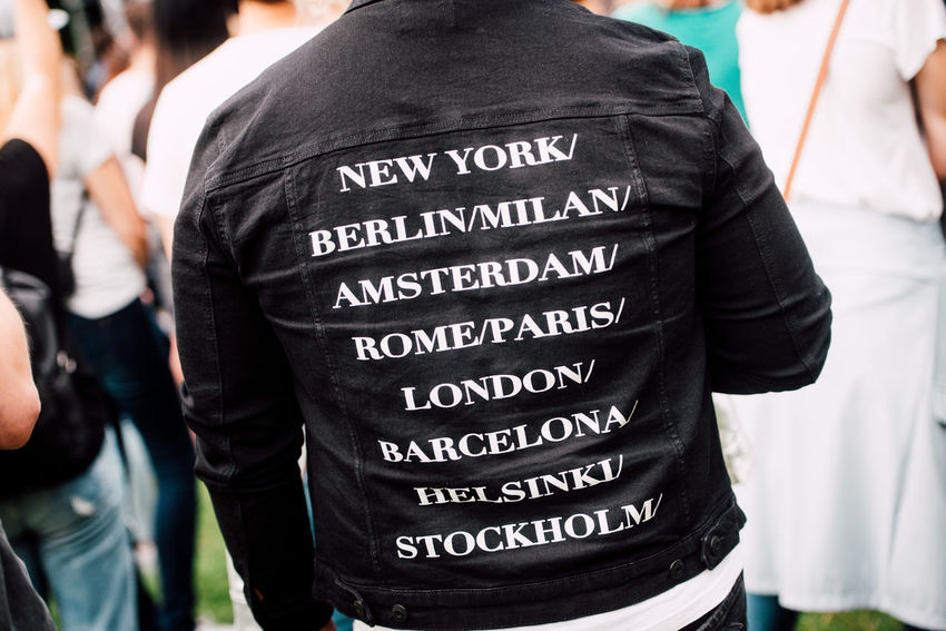 Adult Black Color Cities City Names Close-up Clothing Communication Day Focus On Foreground Group Of People Incidental People Men Outdoors People Real People Rear View Standing Text Western Script