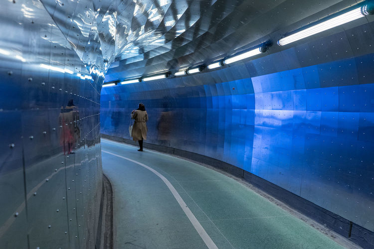 Woman walking in illuminated subway station