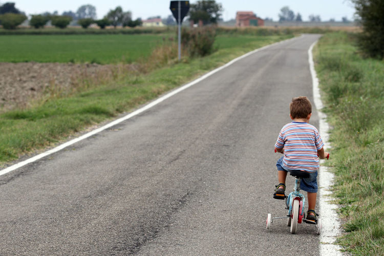 Rear view of boy riding bicycle on road