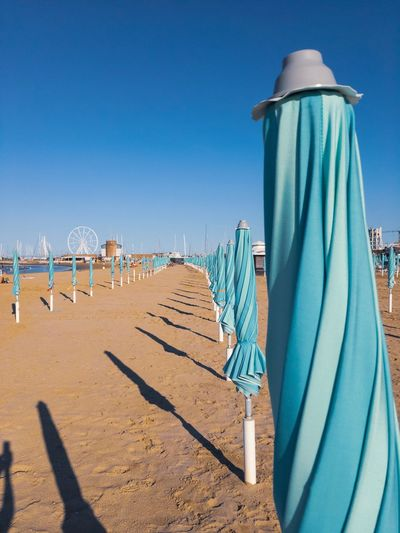 Sun umbrellas closed on the beach on the Adriatic coast of Italy. Rimini.Vertical Banner EyeEm Selects Italy Row Adria Rimini Season  Rimini, Italy Adriatic Sea Nature_collection EyeEm Best Shots Sky Sunlight Sand Clear Sky Land Blue Nature Beach Day Shadow Sunny No People Outdoors Architecture Building Exterior Protection Sea Water Built Structure Security