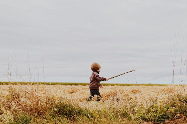 Boy holding stick while walking on grassy field against cloudy sky
