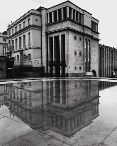 Black and white picture of a vintage building in the old city center of downtown Brussels reflected in the water of a fountain Built Structure Architecture Building Exterior Building Water Reflection City Day Street Waterfront Nature Window No People Sky Outdoors Reflecting Pool Lake Transportation Clear Sky