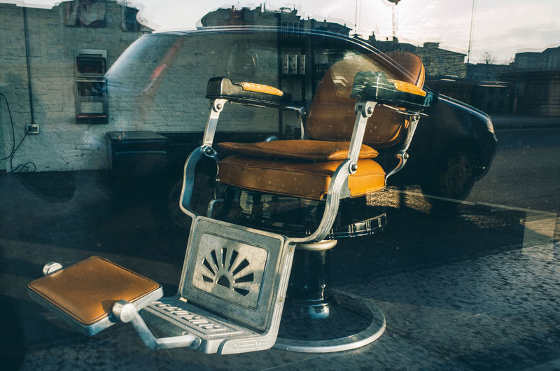 Old-fashioned empty barber chair in salon seen from window glass