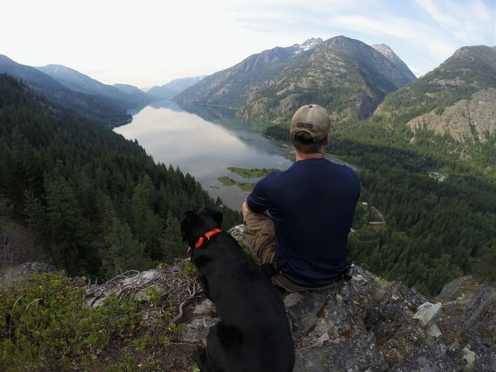 High angle view of man and black dog sitting on mountain against lake chelan