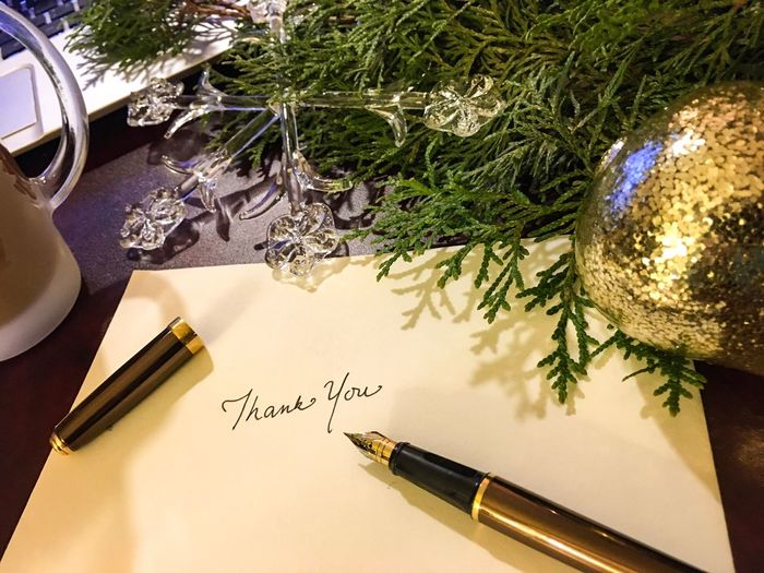 High angle view of pen with envelope by christmas decoration on table