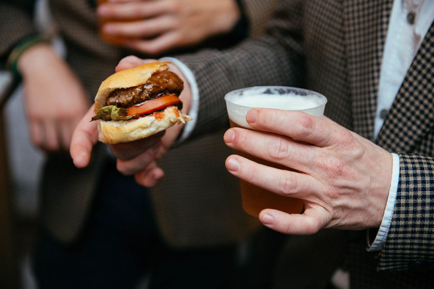 Beer Burger Adult Bar Food Burger Burgers Business Close-up Fast Food Finger Food Food And Drink Freshness Hamburger Holding Human Hand Men Midsection People Ready-to-eat Sandwich Take Out Food Unhealthy Eating
