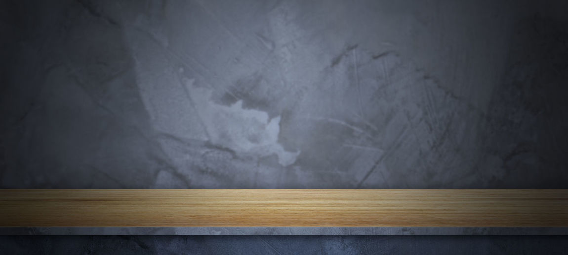 Close-up of empty wooden table against wall