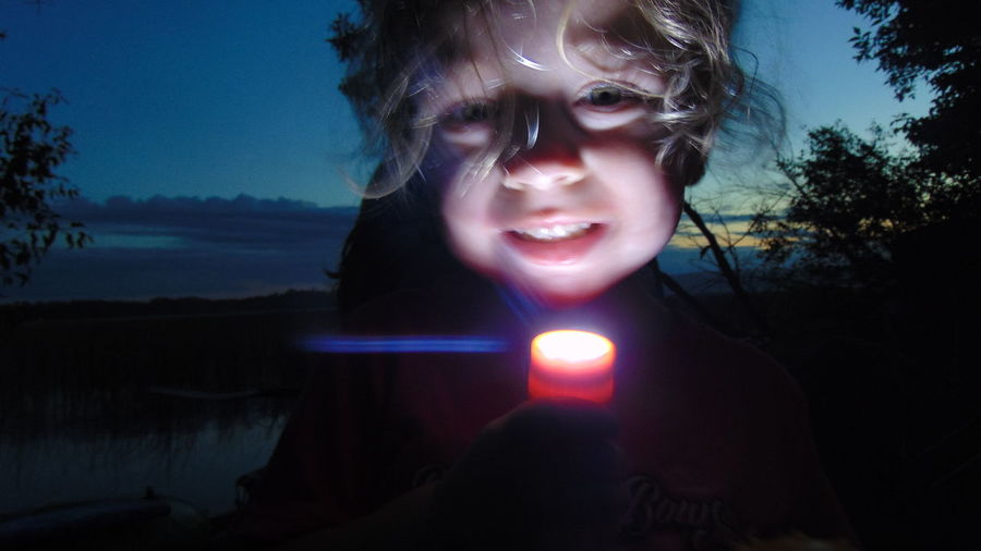 Portrait of girl holding illuminated flashlight against sky at dusk