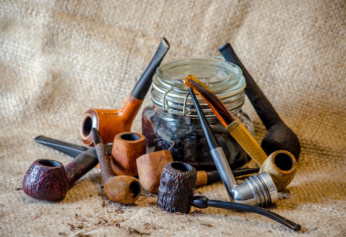 unique old pipe collection with a jar of tobacco, all on a burlap backdrop Objects Retro Tobacco Tobacco Pipe Briar Burlap Background Closeup Collection Craftsmanship  Ebonite Enjoyment Glass Jar Of Tobacco Habit Hand Made Handiwork Lifestyles Metal Nicotine Old Pipe Pipe Collector Smoking Pipe Still Life Vintage Vulconite
