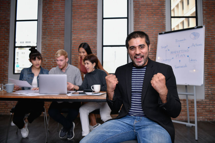 Business concept. Businessmen are shouting with joy. Business people are raising their hands for business success. Hands Up Shake Hands Acclaim ARCHITECT Asian  Background Board Business Businessman Businesswoman Casual Business Caucasian Cheerful Colleague Conversation Coworker Dealing Designer  European  Fun Funny Glad Guide Happiness Happy High Five Jubilant Lifestyle Man Manager Market Meeting Office Partner People Personal Present Professional Smiling Success Successful Successfully Suggest Team Teamwork Togetherness Woman Work Worker Young Adult