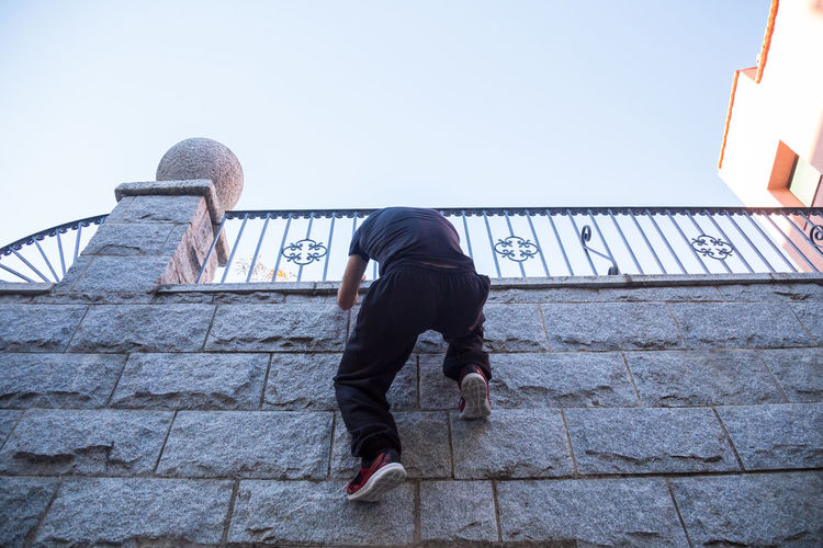 Full Length Of Man Climbing On Wall Against Clear Sky