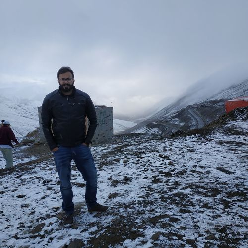 Full Length Portrait Of Young Man Standing In Snowcapped Mountain