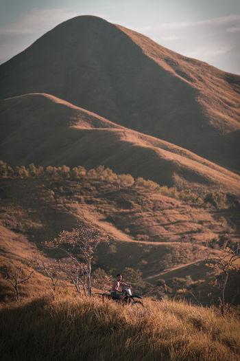Man biking amidst field against mountain