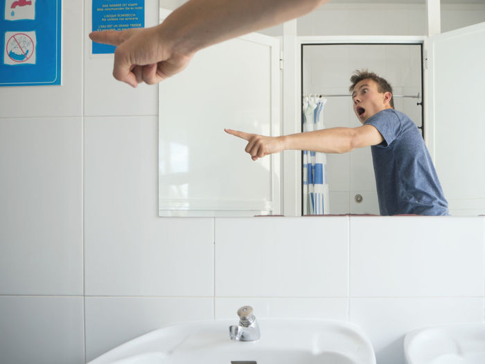 Shocked man gesturing at sign board while standing in bathroom