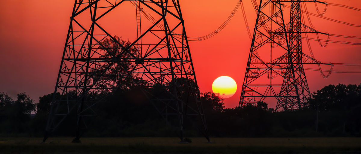 Silhouette electricity pylon against sky during sunset