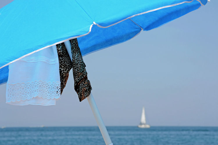 beach umbrella with towel hanging Sea Water Sky Horizon Over Water Sailboat Blue Clear Sky Outdoors Tranquility Umbrella Clothes Sailing Adriatic Sea Italy Italian Beach Beach Life Vacations Relaxing Time Quiet Moments Serenity