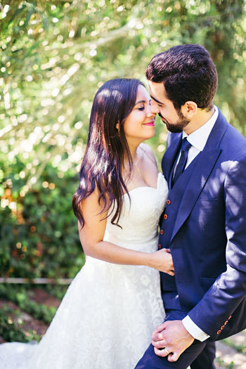 Newlywed Couple Romancing While Standing At Park