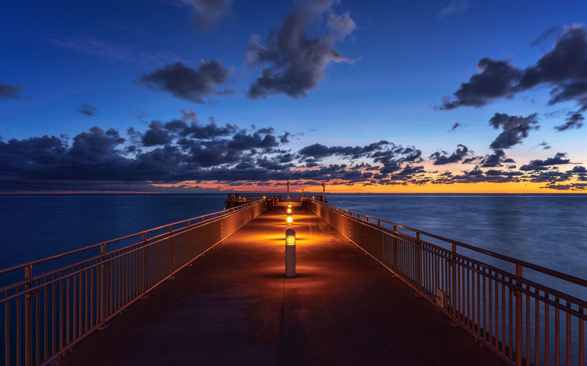 Illuminated bridge over sea against sky during sunset