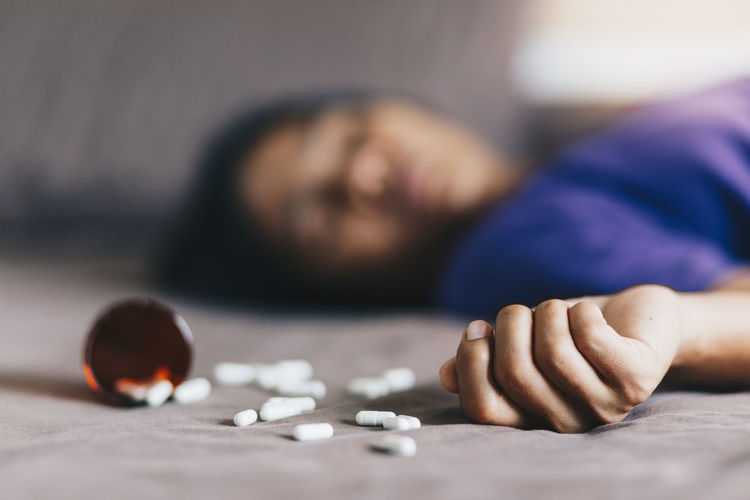 Close-up of pills with woman lying and attempting suicide on floor