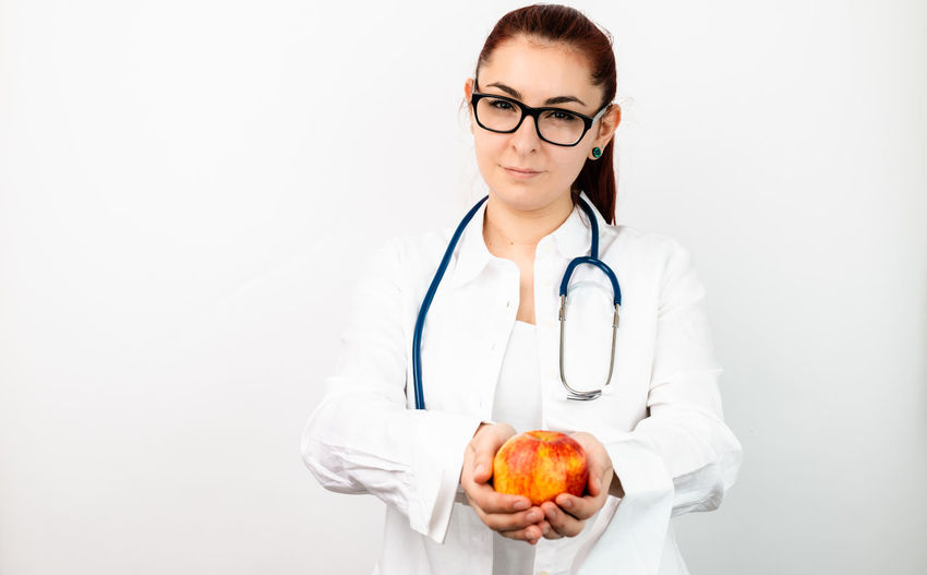 doctor with apple Human Hand White Background Young Women Eyeglasses  Doctor  Portrait Healthcare And Medicine Women Healthy Lifestyle Female Doctor Female Nurse Pediatrician Stethoscope  Healthcare Worker Community Outreach General Practitioner Medical Occupation Nurse