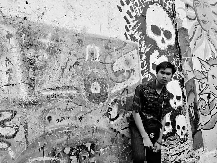 Portrait of smiling young man standing against graffiti wall