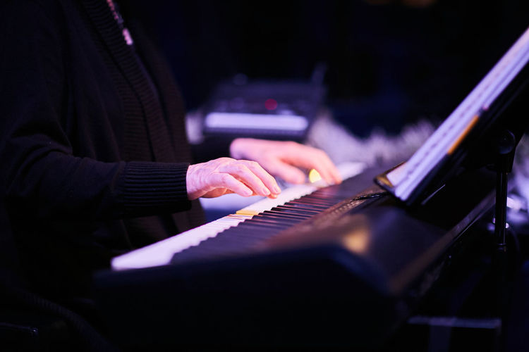 Cropped Wrinkled Hands Of Musician Playing Piano