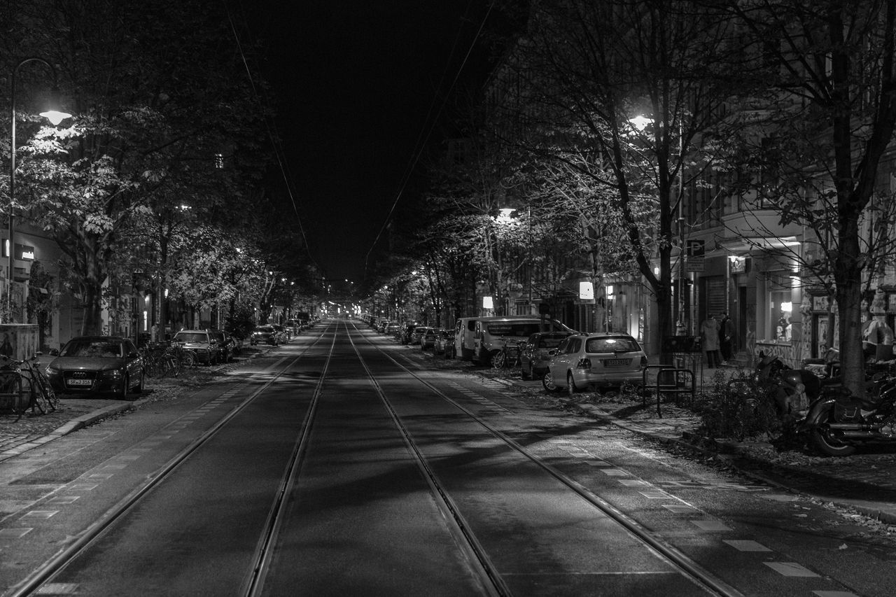 night, illuminated, direction, transportation, the way forward, architecture, tree, building exterior, built structure, city, street, mode of transportation, no people, lighting equipment, street light, track, railroad track, diminishing perspective, road, rail transportation, outdoors, light