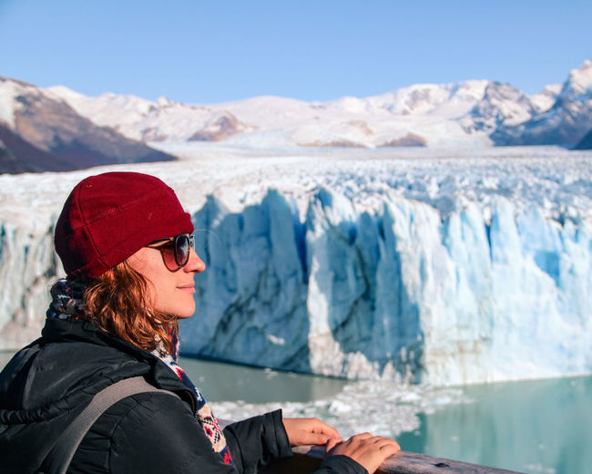 Woman standing on snowcapped mountains during winter in glacier perito moreno