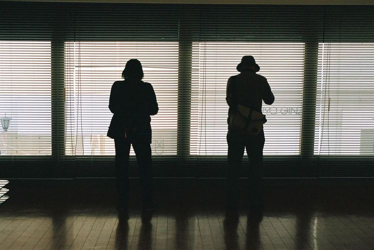Rear View Of Two People Standing Side By Side Against Window