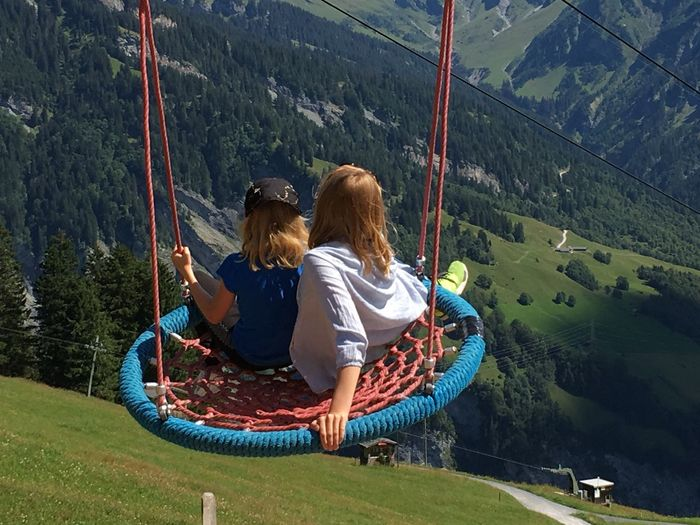 High angle view of siblings swinging on mountain against forest