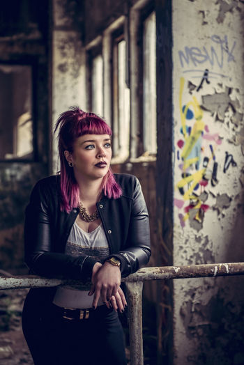 Thoughtful Young Woman Leaning On Railing In Old Building