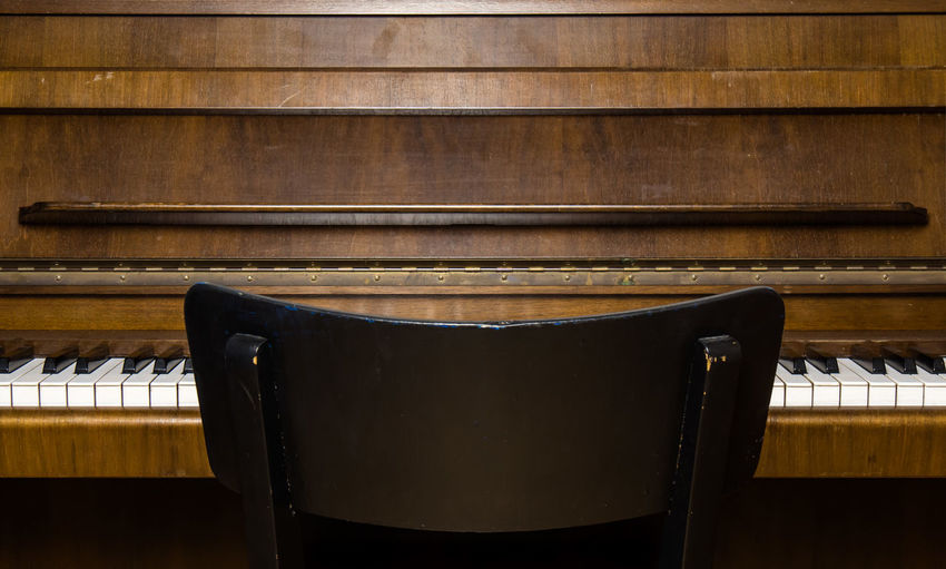 Close-up of chair against piano